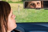 Vrouw stuurprogramma op zoek in de achteruitkijkspiegel — Stockfoto