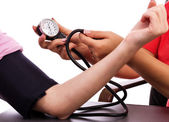 Doctor taking young woman blood pressure — Stock Photo