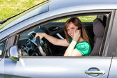 Smiling young woman using smart phone while driving — Stock Photo