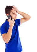 Portrait of a young man talking on the phone with hand on forehe — Stock Photo