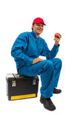Worker sitting on the toolbox with an apple in hand — Stock Photo
