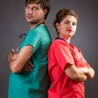 Foto Stock: Serious team of two doctors standing back to back with arms fold