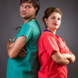 Stock Photo: Serious team of two doctors standing back to back with arms fold