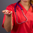 Female doctor or nurse with stethoscope holding pills in her ha — Stock Photo #28108093