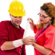Female doctor nurse putting a bandage to a construction worker — Stock Photo