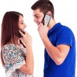 Close-up of a young couple talking on mobile phones — Stock Photo #28108215