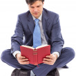Stock Photo: Business msitting cross-legged and reading