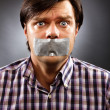 Stock Photo: Young mwith duct tape over his mouth