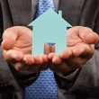 Business man holding a model of a house in his hands — Stock Photo