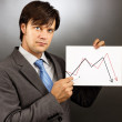 Businessman drawing a falling graph of stock market — Stock Photo #28109159
