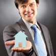 Young business man holding a model of a house on his palm — Stock Photo