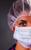 Close-up portrait de jolie infirmière ou un médecin avec un masque chirurgical une — Photo