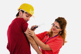 Female doctor nurse putting a syringe to a scared worker — Stock Photo