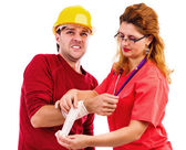 Female doctor putting a bandage to a worker hand, injure — Stock Photo