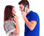 Close-up of a young couple talking on mobile phones — Stock Photo