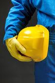 Yellow hardhat under arm — Stock Photo