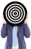 Businessman covering his face with a dartboard — Stock Photo