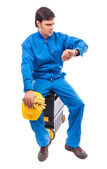 Worried construction worker looking at watch with serious expre — Stock Photo