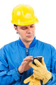 Portrait of a young construction worker using mobile phone — Stock Photo