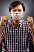 Angry young man with duct tape over his mouth — Stock Photo