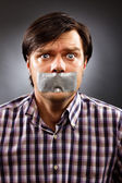 Young man with duct tape over his mouth — Stock Photo