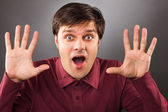 Young man with astonished expression and hands up — Stock Photo