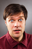 Young handsome man with astonished expression — Stock Photo
