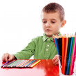 Cute little boy with many crayons sitting at the table — Stock Photo #28626109