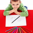 Stock Photo: Happy little boy at table drawing with crayons and looking u