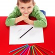 Happy little boy at the table drawing with crayons and looking u — Stock Photo