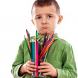 Upset little boy holding many crayons — Stock Photo