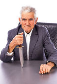 Furious senior with a knife looking at camera — Stock Photo