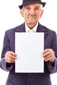 Elderly serious man holding an empty white sheet of paper — Stock Photo