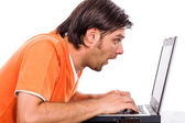 Astonished young man staring at his laptop — Stock Photo