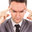Closeup portrait of a young business man with headache rubbing — Stock Photo