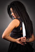 Portrait of an expressive young woman holding a big knife to her — Stock Photo
