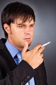 Young businessman during a break smoking a cigarette — Stock Photo