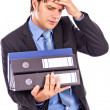 Overwhelmed young businessman holding many folders — Stock Photo