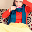 Stock Photo: Young woman having flu and checking a thermometer