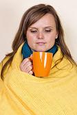 Jonge vrouw bedekt met een deken, een kopje thee, sittin houden — Stockfoto
