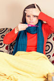 Young woman having flu and checking a thermometer — Stock Photo
