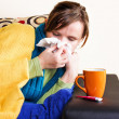 Young woman having flu, blowing her nose — Stock Photo