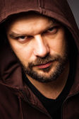 Close-up portrait of threatening man with beard wearing a hood — Stock Photo