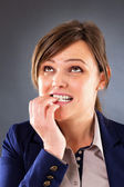 Closeup portrait of a nervous young businesswoman biting her fin — Stock Photo