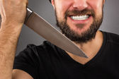 Closeup portrait of a threatening man with beard holding a knife — Stock Photo