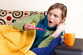 Expressive young woman having flu and checking thermometer — Stock Photo