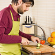 Handsome young man in the kitchen cutting vegetables — Stock Photo #40002507