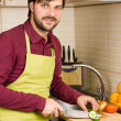 Handsome young man in the kitchen with apron cutting vegetables — Stock Photo #40002685
