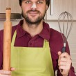 Smiling young man with apron holding a beater and a rolling pin — Stock Photo #40002847