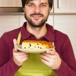 Smiling young man with apron holding a plate with homemade cake — Stock Photo #40002865